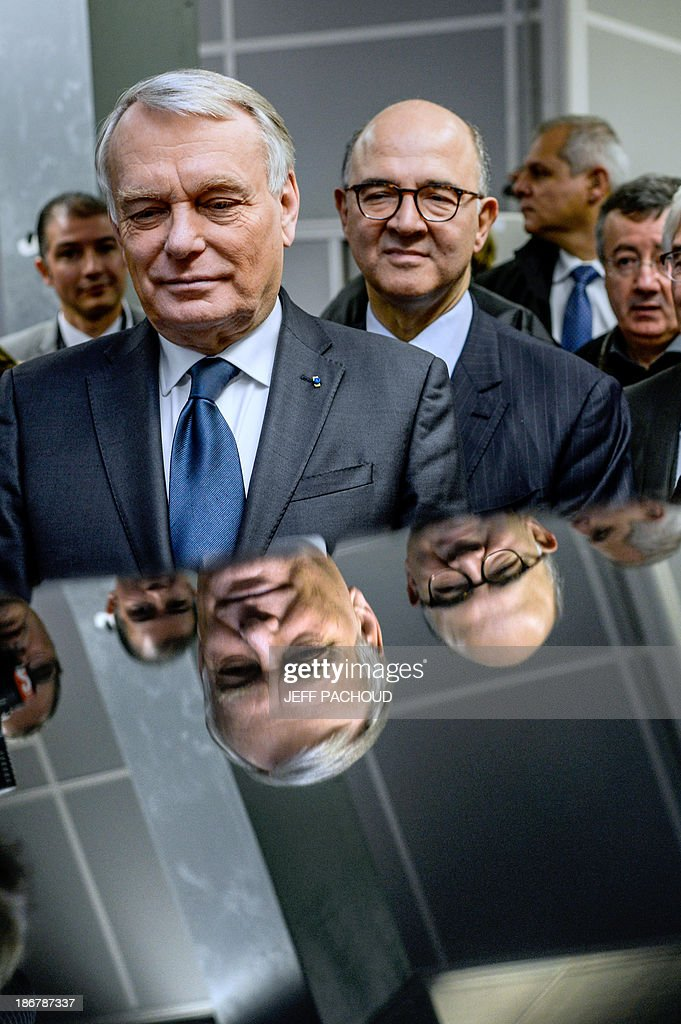 French Prime Minister Jean-Marc Ayrault (L) visits a Focal factory flanked by French Economy, Finance and Foreign Trade Minister Pierre Moscovici (R), on November 4, 2013 in Saint-Etienne, center France.