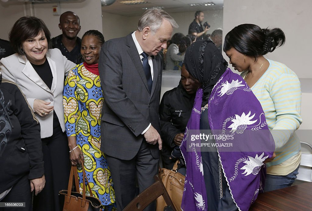 French Prime Minister Jean-Marc Ayrault (C) visits a Salvation Army emergency lodging centre with French Junior Minister for Disabled People Marie-Arlette Carlotti (L) in Paris on April 4, 2013.