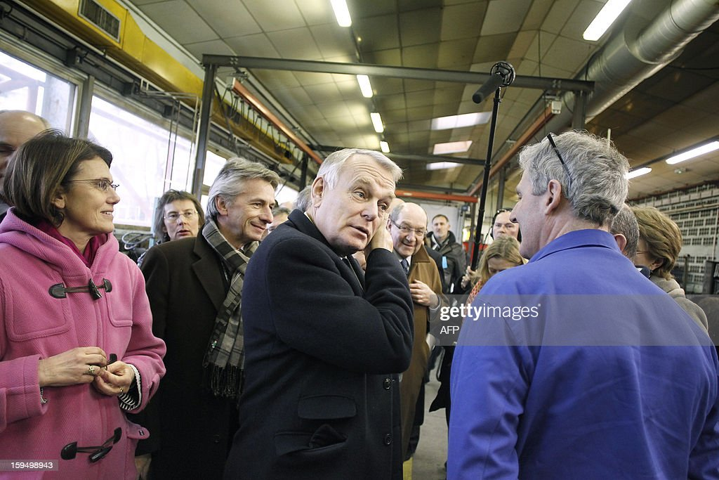 French Prime Minister Jean-Marc Ayrault (C) visits a workshop in a center for adult learning (Afpa - formation pour adultes), on January 14, 2013 in Caen, Normandy.