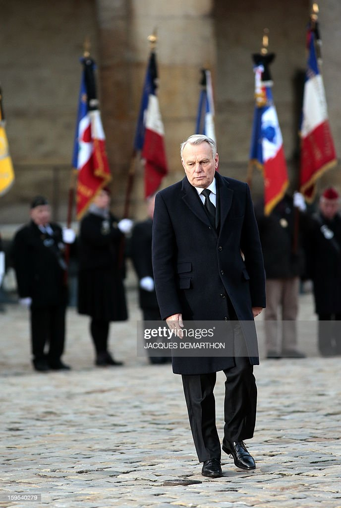 French Prime Minister Jean-Marc Ayrault walks during a funeral service for French air force lieutenant Damien Boiteux at the Invalides courtyard in Paris, on January 15, 2013. French pilot Damien Boiteux was killed on January 11 during a helicopter raid launched to support Mali ground troops in the battle for the key town of Kona, and to prevent Islamist groups controlling northern Mali from advancing toward the capital Bamako. AFP PHOTO / POOL / JACQUES DEMARTHON