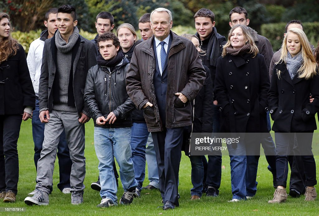 French Prime Minister Jean-Marc Ayrault (C) walks with students during a tree planting on the grounds of Hotel Matignon in Paris on November 29, 2012.