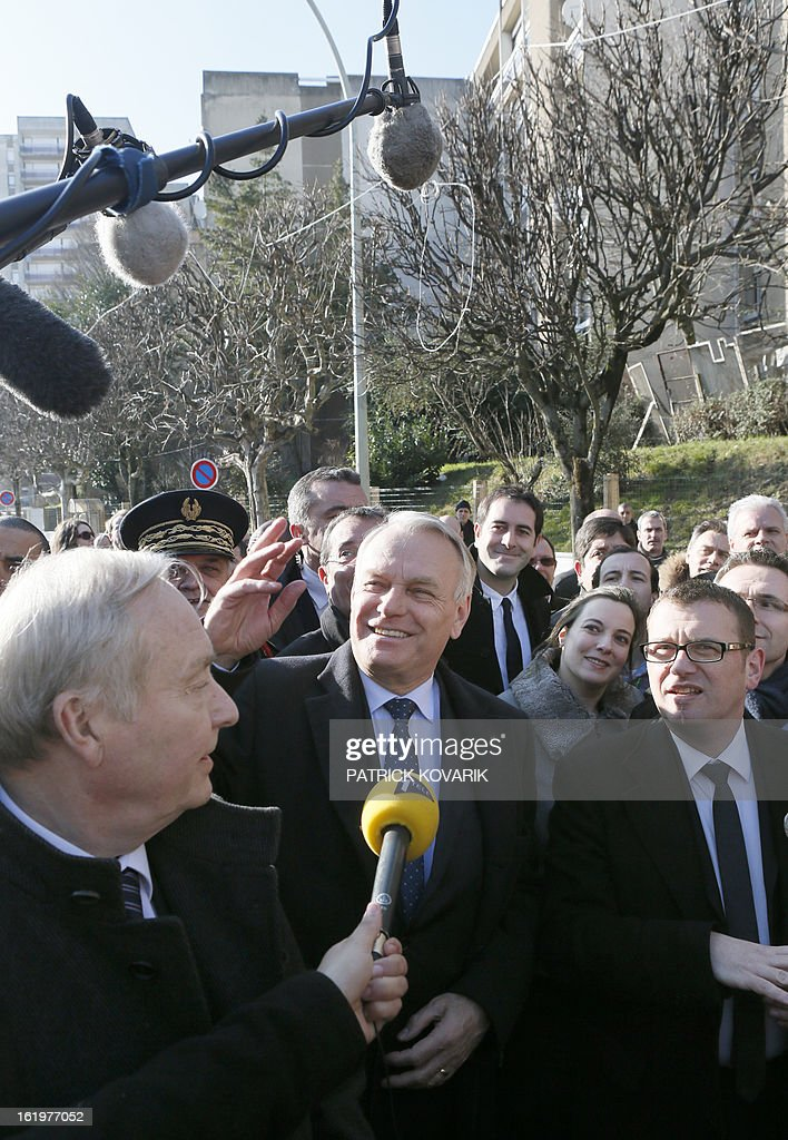 French Prime Minister Jean-Marc Ayrault (C) waves, surrounded by the former mayor of Clichy-sous-Bois Claude Dilain (L) and the current mayor Olivier Klein (R) on February 18, 2013 during his visit to Clichy-sous-Bois, northern suburb of Paris, as part of the French government's urban policy.