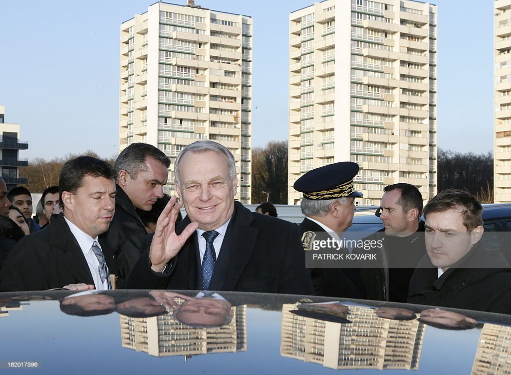 French Prime Minister Jean-Marc Ayrault (C) waves to residents during a visit to Clichy-sous-Bois, northern suburb of Paris on February 18, 2013, as part of the French government's urban policy.