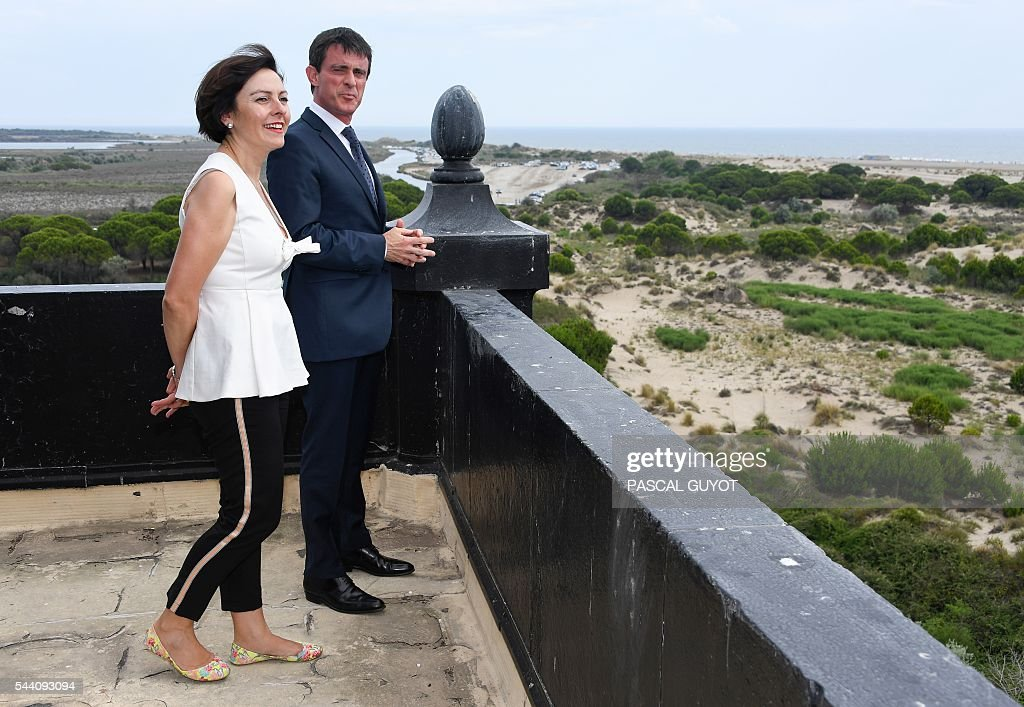 French Prime Minister Manuel Valls (R) and Carole Delga, president of the regional council Occitanie pose as they visit the lighthouse of Espiguette beach, southern France, on July 1, 2016. / AFP / PASCAL