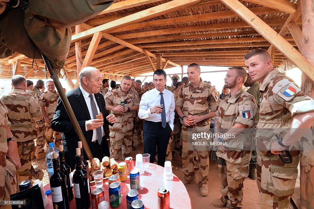 French Prime Minister Manuel Valls and French Defence Minister JeanYves Le Drian share a lunch with soldiers during a visit to the troops of France's...