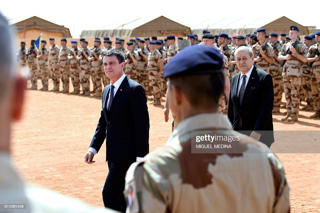French Prime Minister Manuel Valls and French Defence Minister JeanYves Le Drian review the troops on February 19 2016 in Gao northern Mali during a...