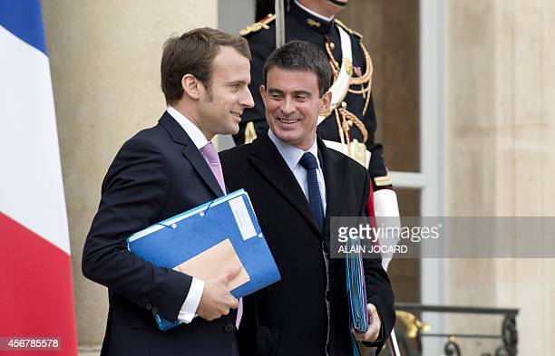 French Prime Minister Manuel Valls and French Economy and Industry minister Emmanuel Macron leave a cabinet meeting focusing on employment on October...