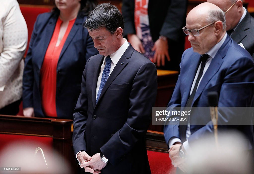 French Prime minister Manuel Valls (L) and French junior minister for Parliamentary Relations Jean-Marie Le Guen observe a minute of silence for the victims of the attacks at Istanbul's Ataturk airport during the questions to the government session on June 29, 2016 at the French National Asssembly in Paris. / AFP / Thomas SAMSON