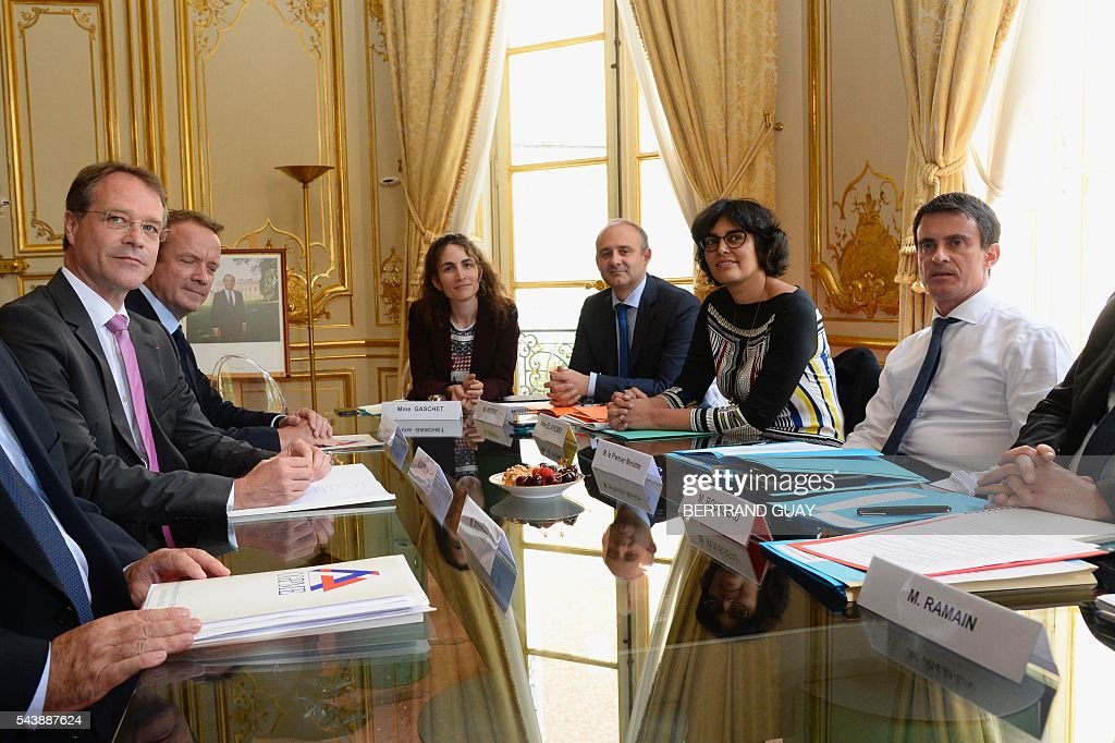 French Prime Minister Manuel Valls (R) and French Labour Minister Myriam El Khomri (2ndR) attend a meeting with the head of France's small and medium-sized employers' organisation (CGPME), Francois Asselin (L) on June 30, 2016 at the Hotel Matignon in Paris. French President Francois Hollande said last week that his Socialist government would 'go all the way' to enact the labour reforms, which are seen by critics as too pro-business and a threat to cherished workers' rights. / AFP / BERTRAND