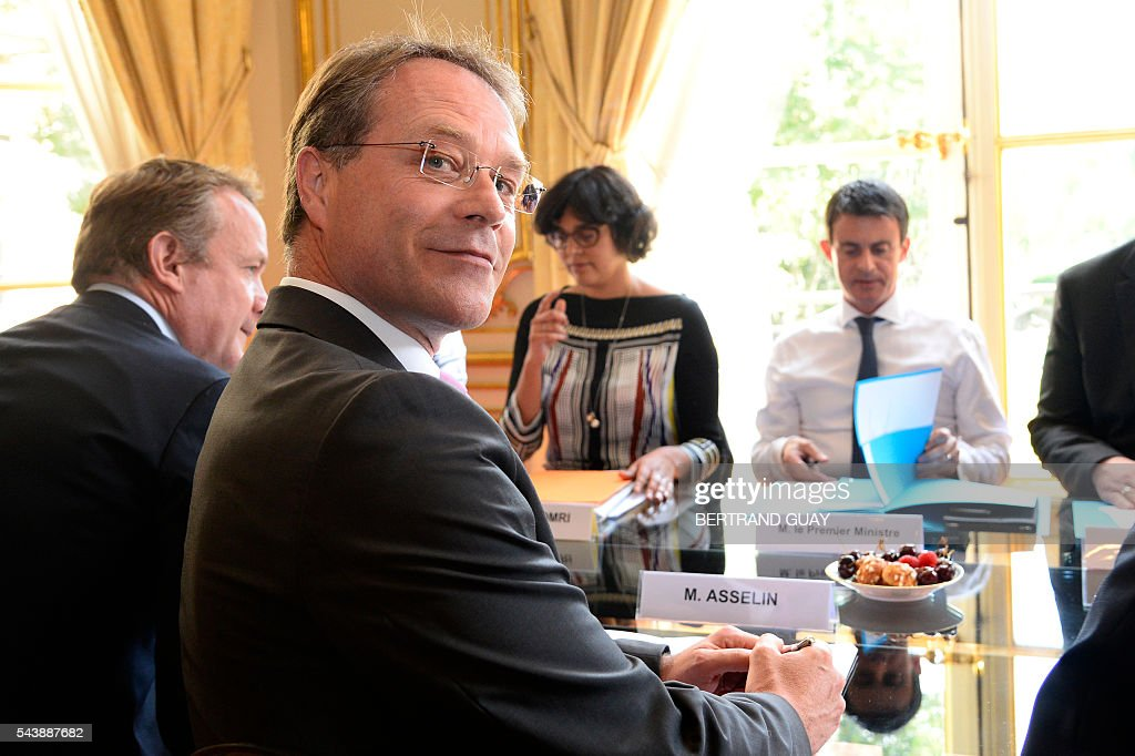 French Prime Minister Manuel Valls (R) and French Labour Minister Myriam El Khomri (C) attend a meeting with the head of France's small and medium-sized employers' organisation (CGPME), Francois Asselin (Front) on June 30, 2016 at the Hotel Matignon in Paris. French President Francois Hollande said last week that his Socialist government would 'go all the way' to enact the labour reforms, which are seen by critics as too pro-business and a threat to cherished workers' rights. / AFP / BERTRAND