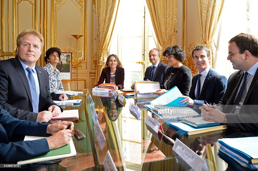 French Prime Minister Manuel Valls (2ndR) and French Labour Minister Myriam El Khomri (3rd R) attend a meeting with the head of the French Confederation of Management General Confederation of Executives (Confederation française de l'encadrement-Confederation generale des cadres, CFE-CGC) Francois Hommeril (L) on June 30, 2016 at the Hotel Matignon in Paris. French President Francois Hollande said last week that his Socialist government would 'go all the way' to enact the labour reforms, which are seen by critics as too pro-business and a threat to cherished workers' rights. / AFP / BERTRAND