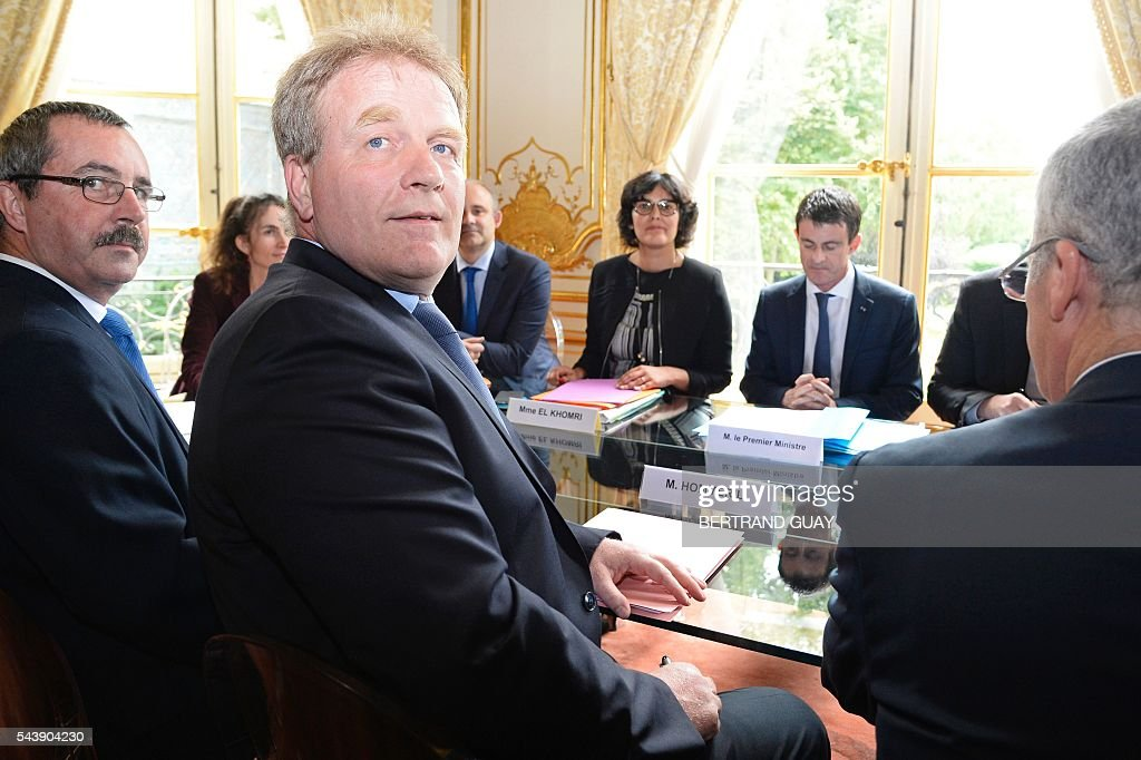 French Prime Minister Manuel Valls (2ndR Rear) and French Labour Minister Myriam El Khomri (Rear C) attend a meeting with the head of the French Confederation of Management General Confederation of Executives (Confederation française de l'encadrement-Confederation generale des cadres, CFE-CGC) Francois Hommeril (Front) on June 30, 2016 at the Hotel Matignon in Paris. French President Francois Hollande said last week that his Socialist government would 'go all the way' to enact the labour reforms, which are seen by critics as too pro-business and a threat to cherished workers' rights. / AFP / BERTRAND
