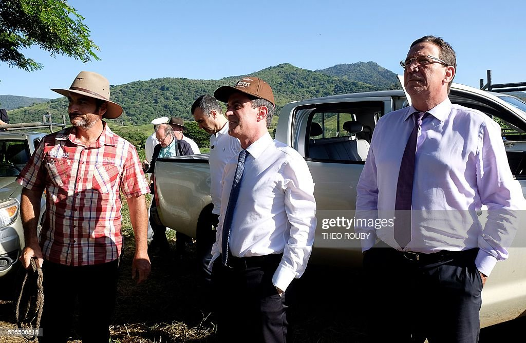 French Prime Minister Manuel Valls (C) and French member of Parliament of New Caledonia Philippe Gomes (R) visit the Delathiere family farm on April 30, 2016 in La Foa, as part of Valls' visit to the French Pacific territory of New Caledonia. / AFP / Th��o Rouby