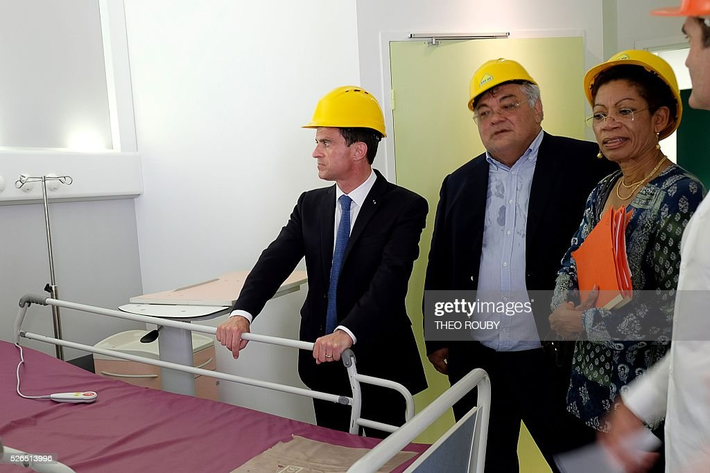 French Prime Minister Manuel Valls (L) and French Minister for Overseas Territories George Pau-Langevin (R) visit the construction site of a hospital April 30, 2016 in Kone, as part of their visit to the French Pacific territory of New Caledonia. / AFP / Th��o Rouby