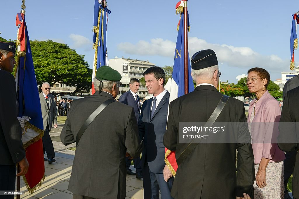 French Prime Minister Manuel Valls and French Overseas Territories Minister George Paul-Langevin shake hands as they arrive at the place Bir-Hakeim in Noumea during a wreath lane ceremony at the wall memorial on April 29, 2016. / AFP / Fred Payet