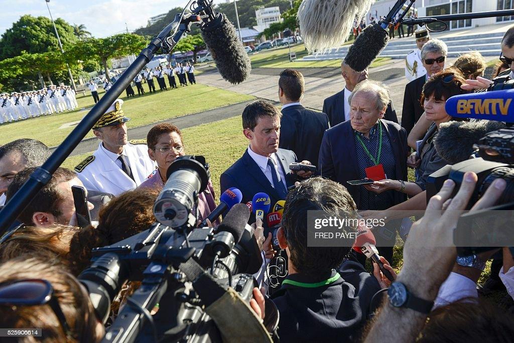 French Prime Minister Manuel Valls (C) and French Overseas Territories Minister George Paul-Langevin (L) speak to the press at the place Bir-Hakeim in Noumea during a wreath lane ceremony at the wall memorial on April 29, 2016. / AFP / Fred Payet