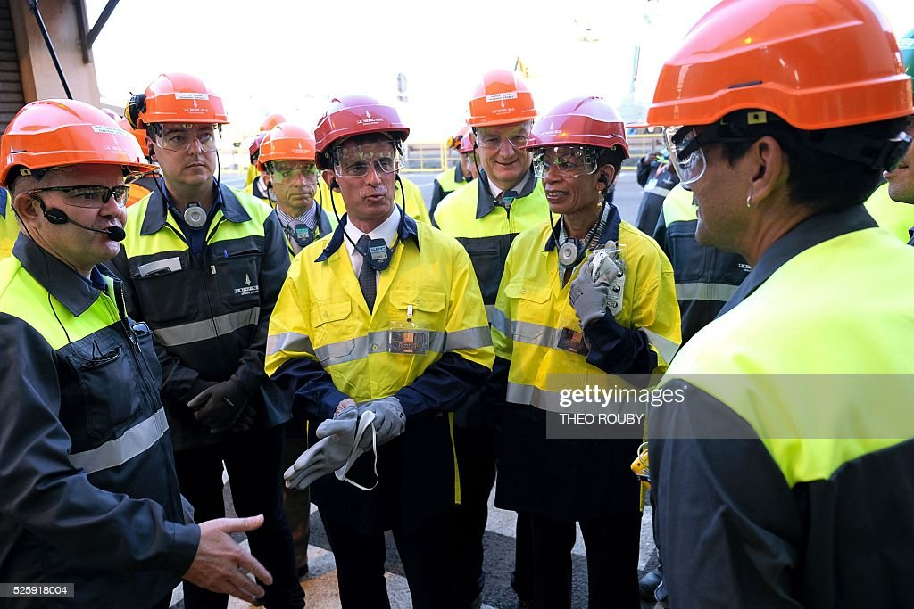 French Prime Minister Manuel Valls (C) and French Overseas Territories Minister George Pau-Langevin (R) meet metallurgic factory SLN's workers as they visit the infrastructure with SNL General director Jerome Fabre in Noumea on April 29, 2016. Valls said France would be willing to loan 200 millions euros to save the SLN factory, the main producer of nickel in New Caledonia. / AFP / THEO