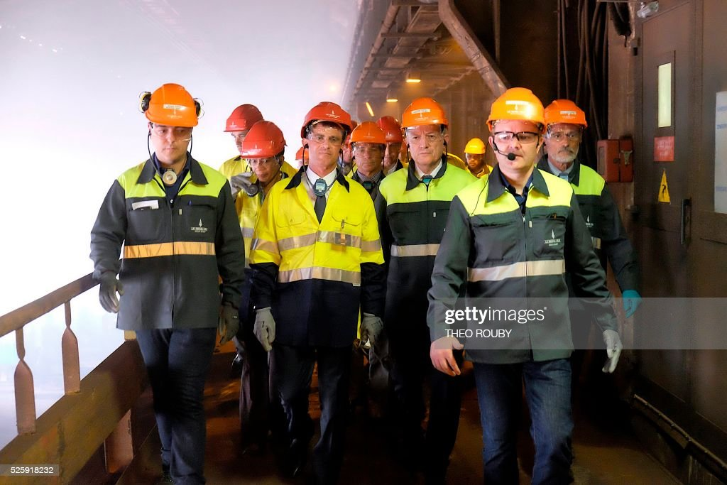French Prime Minister Manuel Valls (2nd row C) and French Overseas Territories minister George Pau-Langevin (3rd row L) visit the metallurgic factory SLN with French CEO of Eramet Patrick Buffet (2nd row R) in Noumea on April 29, 2016. Valls said France would be willing to loan 200 millions euros to save the SLN factory, the main producer of nickel in New Caledonia. / AFP / THEO