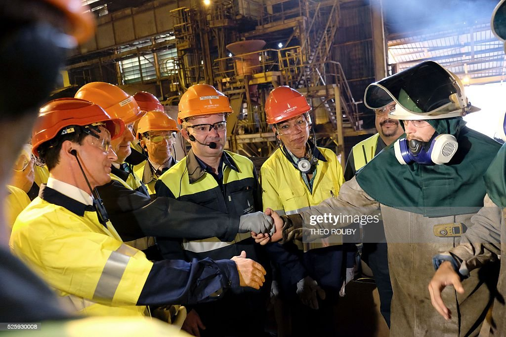 French Prime Minister Manuel Valls (L) and French Overseas Territories Minister George Pau-Langevin (C) meet metallurgic factory SLN's workers during their visit in Noumea on April 29, 2016. Valls said France would be willing to loan 200 millions euros to save the SLN factory, the main producer of nickel in New Caledonia. / AFP / THEO