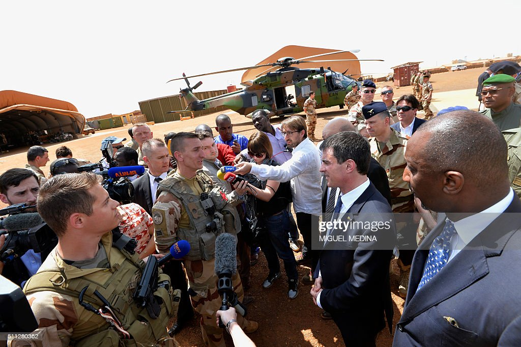 French Prime Minister Manuel Valls and Mali Defence Minister Tieman Hubert Coulibaly listen to soldiers during his visit to the troops of France's...