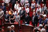 French Prime minister Manuel Valls and members of parliament stand as they observe a minute of silence in memory of the victims of the attack in Nice...