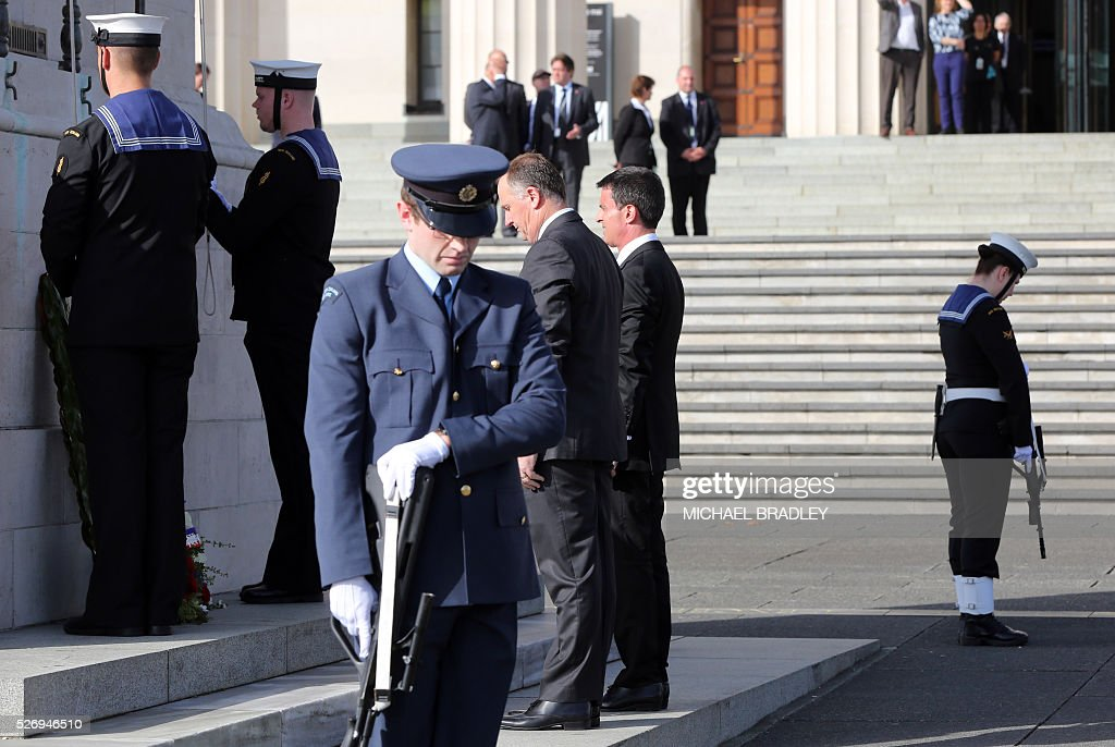 French Prime Minister Manuel Valls (R) and New Zealand Prime Minster John Key (C) attend the Wreath Laying Ceremony at the Auckland War Memorial Museum in Auckland on May 2, 2016. Valls arrived in New Zealand on May 1st after visiting the French Pacific territory of New Caledonia, with officials in his delegation confirming that he will detour to Australia later today. / AFP / MICHAEL