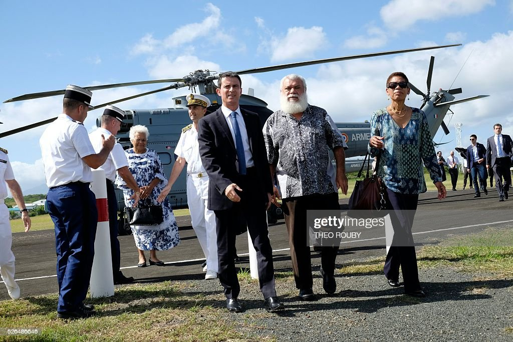 French Prime minister Manuel Valls (C) and Overseas minister George Pau-Langevin (R) are welcomed by president of the North Province of New Caledonia Paul Neaoutyine (2ndR) upon their arrival in Kone, on April 30, 2016, as part of Valls' visit to the French Pacific territory. The visit comes amid political tension about New Caledonia's future and economic uncertainty following the sharp drop in the price of nickel. With the territory bound to have an independence referendum by 2018, Manuel Valls called on the territory's leaders not to waste time in useless skirmishes. / AFP / Th��o Rouby