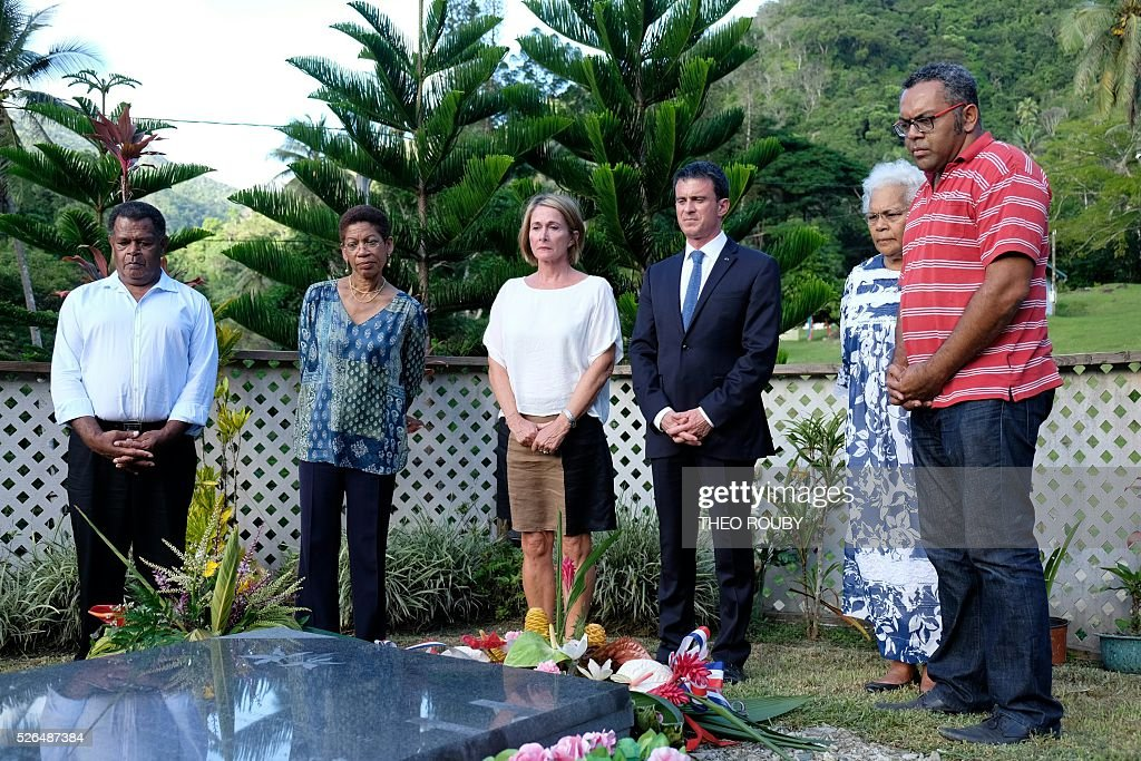 French Prime minister Manuel Valls (3rdR) and Overseas minister George-Pau Langevin (2ndL) stand in front of the grave of Jean-Marie Tjibaou, late leader of the Kanak independence movement and politician assassinated in 1989 as part of his visit to the Tiendanite tribe, on April 30, 2016 in Tiendanite, as part of his trip to the French Pacific territory of New Caledonia. / AFP / POOL / Th��o Rouby