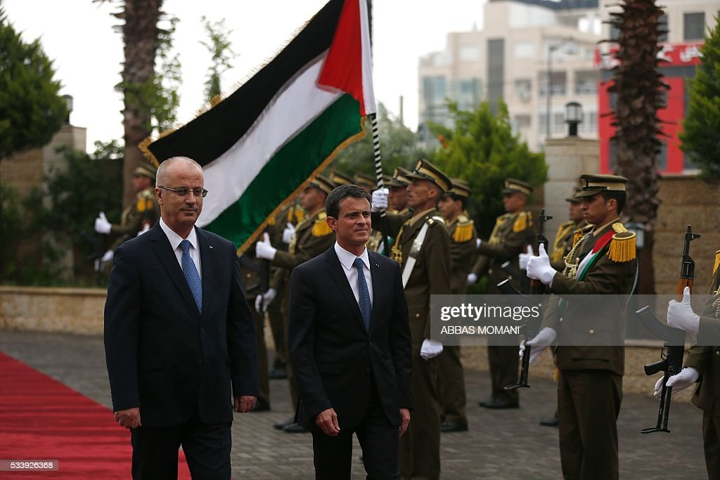 French Prime Minister Manuel Valls (C) and Palestinian prime minister Rami Hamdallah (L) arrive for a meeting in the West Bank city of Ramallah, on May 24, 2016. / AFP / ABBAS
