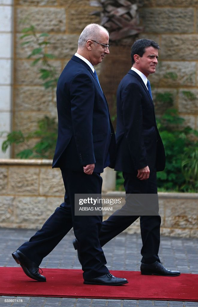 French Prime Minister Manuel Valls and Palestinian prime minister Rami Hamdallah (L) arrive for a meeting in the West Bank city of Ramallah, on May 24, 2016. Palestinian prime minister Rami Hamdallah dismissed an Israeli proposal for direct negotiations instead of a French multilateral peace initiative, calling it an attempt to 'buy time'. / AFP / ABBAS