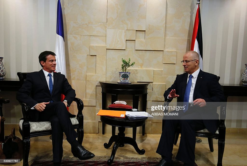French Prime Minister Manuel Valls and Palestinian prime minister Rami Hamdallah (R) speak during a meeting in the West Bank city of Ramallah, on May 24, 2016. Palestinian prime minister Rami Hamdallah dismissed an Israeli proposal for direct negotiations instead of a French multilateral peace initiative, calling it an attempt to 'buy time'. / AFP /