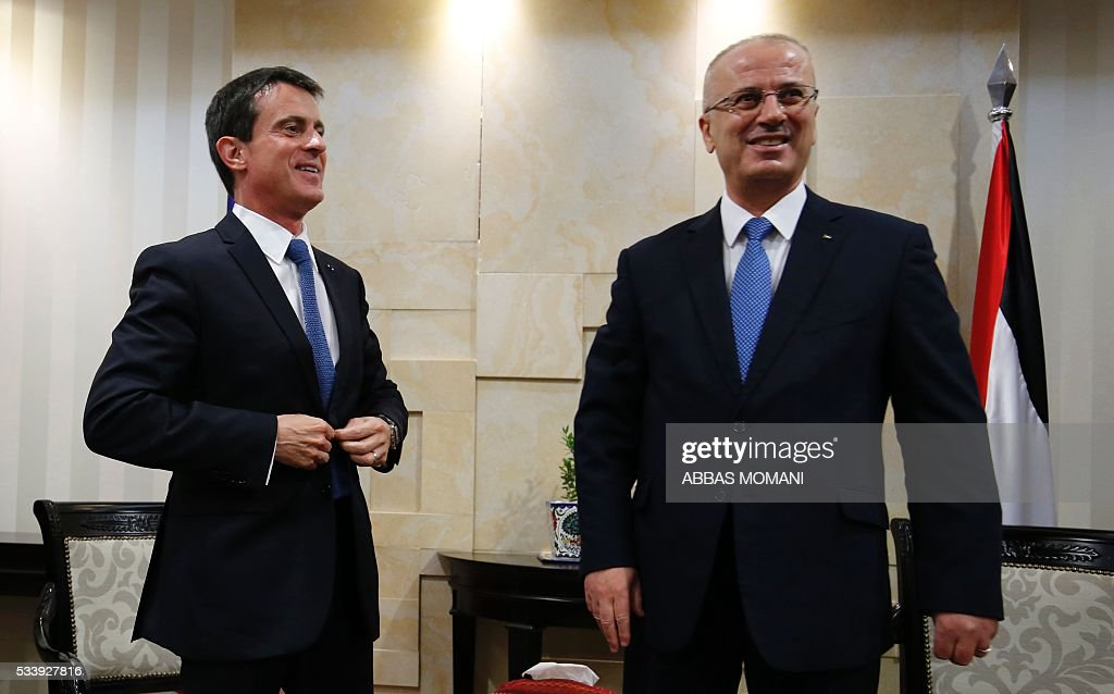 French Prime Minister Manuel Valls and Palestinian prime minister Rami Hamdallah (R) speak following a meeting in the West Bank city of Ramallah, on May 24, 2016. Palestinian prime minister Rami Hamdallah dismissed an Israeli proposal for direct negotiations instead of a French multilateral peace initiative, calling it an attempt to 'buy time'. / AFP /