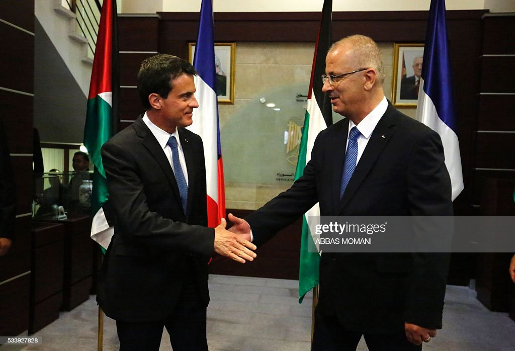 French Prime Minister Manuel Valls and Palestinian prime minister Rami Hamdallah (R) shake hands ahead of a meeting in the West Bank city of Ramallah, on May 24, 2016. Palestinian prime minister Rami Hamdallah dismissed an Israeli proposal for direct negotiations instead of a French multilateral peace initiative, calling it an attempt to 'buy time'. / AFP /