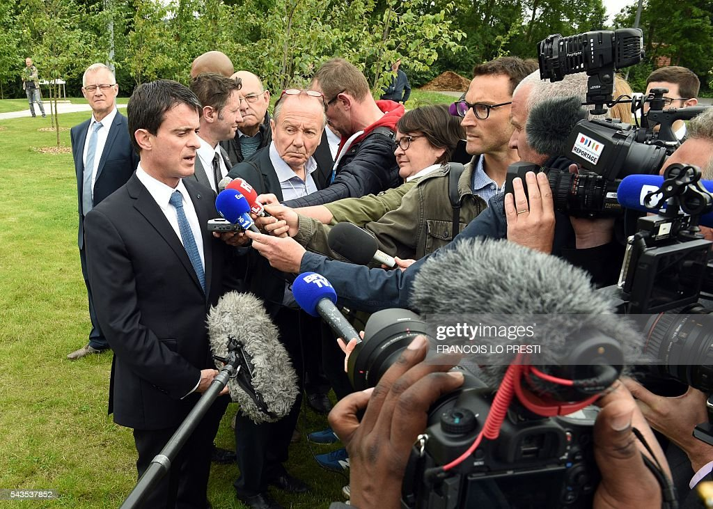 French Prime Minister Manuel Valls (L) answers journalists' questions during a visit to the 'Cite 9' in Lens, on June 29, 2016, dedicated to the rehabilitation of Lens-Lievin mining area and the surroundings, including the renovation of housing. French urban planner Jean-Louis Subileau is in charge of the project and is expected to report next fall. / AFP / FRANCOIS