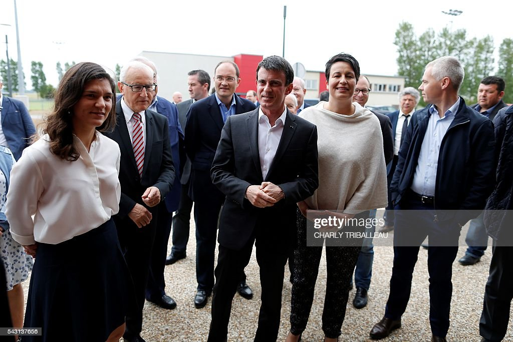 French Prime Minister Manuel Valls (with French Junior minister for Local Authorities Estelle Grelier (R)) arrive to the 'Banquet Republicain' with Seine-Maritime departmental delegate Marie Le Vern (L), on June 26, 2016 in Belleville-sur-Mer, northwestern France. French Prime Minister Manuel Valls on Sunday said he opposed the TTIP transatlantic trade treaty currently under negotiation on the grounds that it was against 'EU interests'. 'No free trade agreement should be concluded if it does not respect EU interests. Europe should be firm,' Valls told members of the governing Socialist Party, adding 'France will be vigilant about this.' / AFP / CHARLY