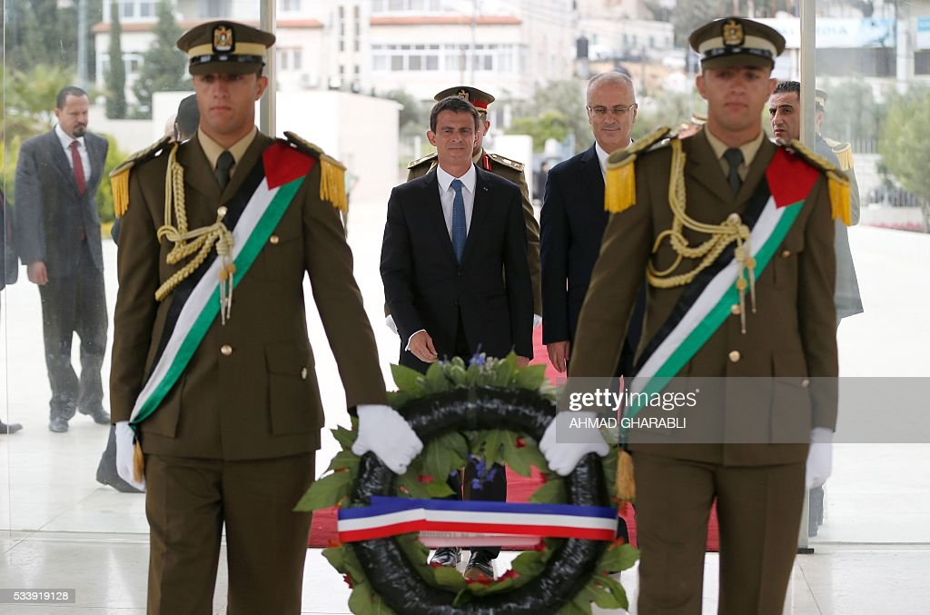 French Prime Minister Manuel Valls (C) arrives with Palestinian prime minister Rami Hamdallah (2-R) to lay a wreath at the tomb of the late Palestinian leader Yasser Arafat at the Muqataa, the Palestinian Authority headquarters, in the West Bank city of Ramallah, on May 24, 2016. / AFP / AHMAD
