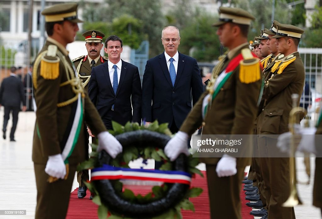 French Prime Minister Manuel Valls (C-L) arrives with Palestinian prime minister Rami Hamdallah (C-R) to lay a wreath at the tomb of the late Palestinian leader Yasser Arafat at the Muqataa, the Palestinian Authority headquarters, in the West Bank city of Ramallah, on May 24, 2016. / AFP / AHMAD
