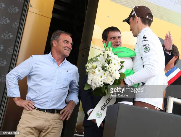French Prime Minister Manuel Valls congratulates Romain Bardet of France and AG2R La Mondiale on the podium for his white jersey while Bernard...