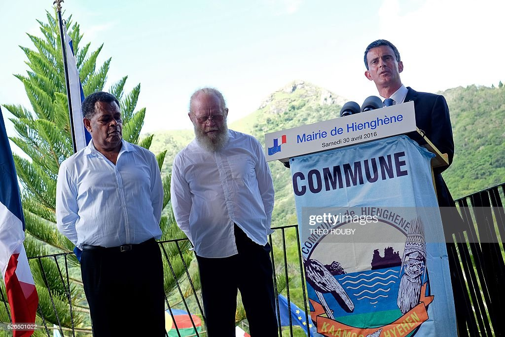 French Prime Minister Manuel Valls (R) delivers a speech flanked by mayor of Hienghene Daniel Goa (L) and president of New Caledonia's Traditions Senate Gilbert Tein (C) on April 30, 2016 in Hienghene, as part of his visit to the French Pacific territory of New Caledonia. / AFP / Th��o Rouby