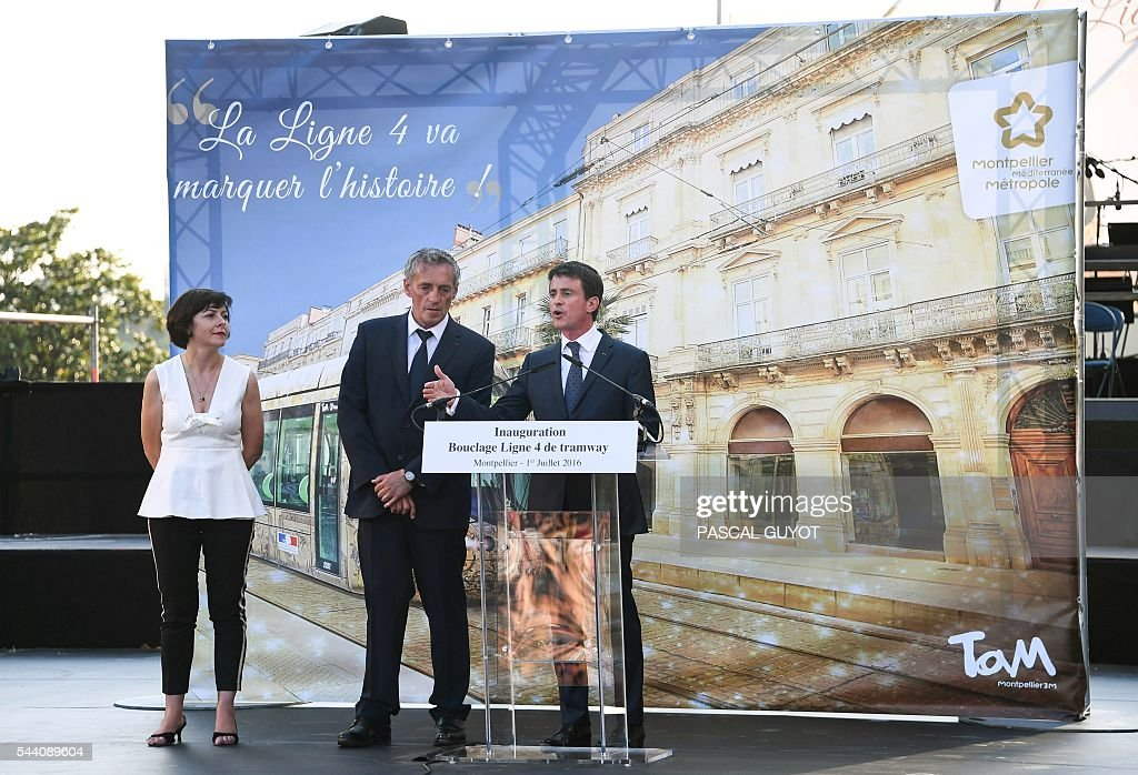 French Prime Minister Manuel Valls (R) delivers a speech next to Mayor of Montpellier Philippe Saurel (C) and Carole Delga, president of the regional council occitanie (L), on July 1, 2016, during the inauguration of the tram line 4 in Montpellier, southern France. / AFP / PASCAL