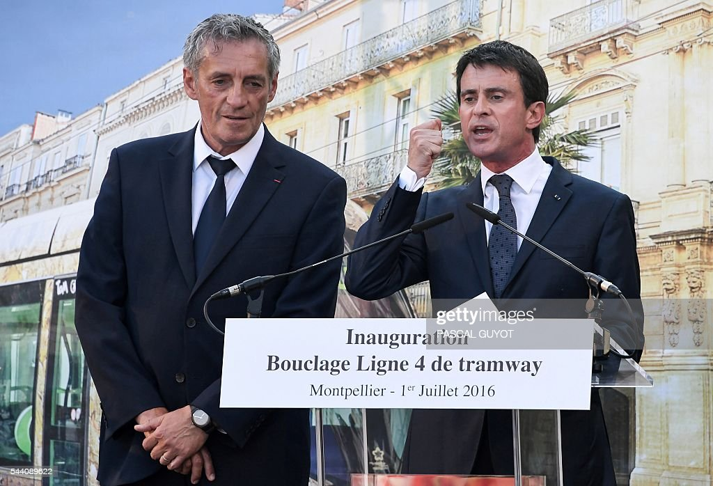 French Prime Minister Manuel Valls (R) delivers a speech next to Mayor of Montpellier Philippe Saurel (L) on July 1, 2016, during the inauguration of the tram line 4 in Montpellier, southern France. / AFP / PASCAL