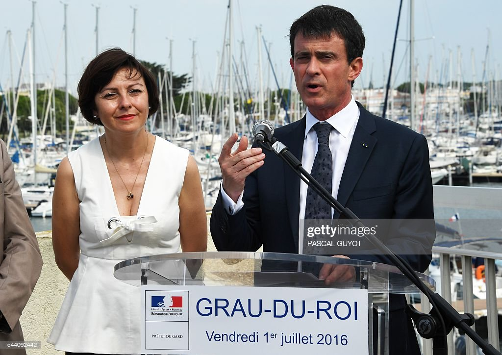 French Prime Minister Manuel Valls (R) delivers a speech next to President of the regional council occitanie (L) Carole Delga on July 1, 2016 delivers a speech on July 1, 2016, during his visit at Le Grau du Roi, southern France. / AFP / PASCAL