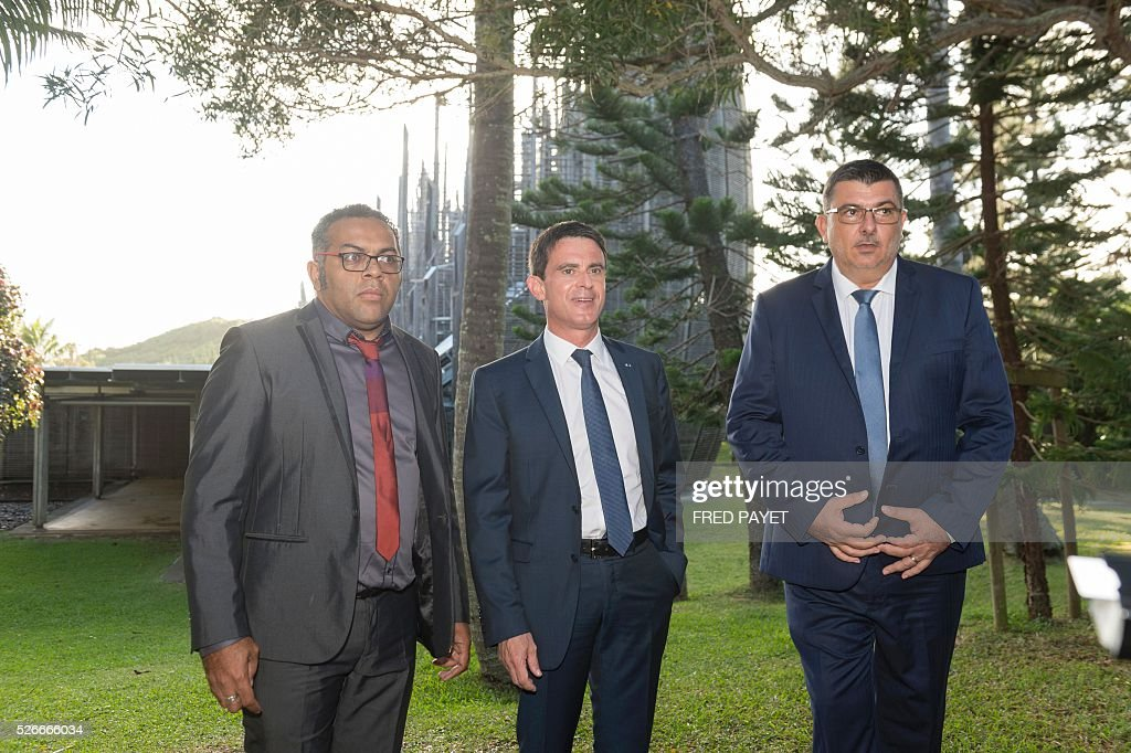French Prime Minister Manuel Valls (C), flanked by Emmanuel Tjibaou (L), son of Kanak independentist leader Jean-Marie Tjibaou, and Philippe Germain (R), President of the Government of New Caledonia, look on during a visit to the Tjibaou Cultural Centre in Noumea, the French Pacific territory of New Caledonia, on May 1, 2016. / AFP / Fred Payet