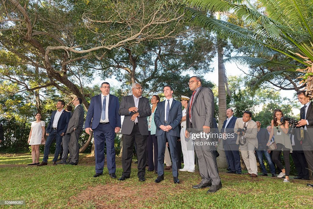 French Prime Minister Manuel Valls (2nd R), flanked by Emmanuel Tjibaou (R), son of Kanak independentist leader Jean-Marie Tjibaou, and Philippe Germain (L), President of the Government of New Caledonia, look on during a visit to the Tjibaou Cultural Centre in Noumea, the French Pacific territory of New Caledonia, on May 1, 2016. / AFP / Fred Payet