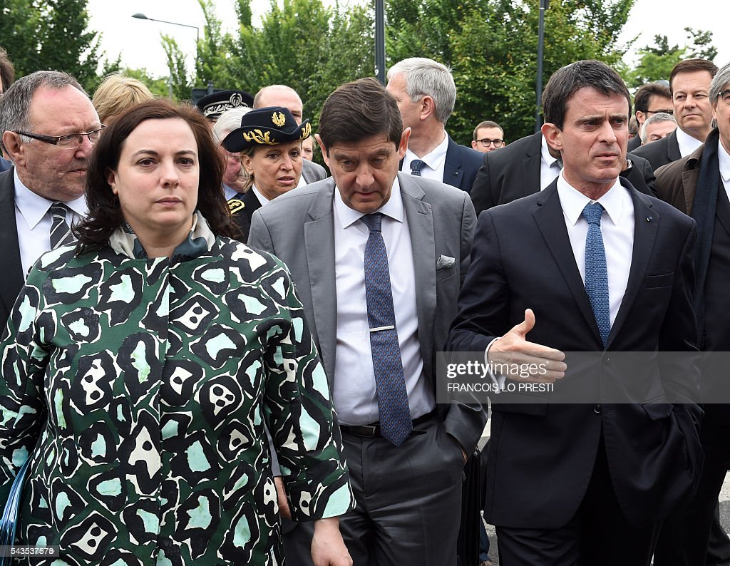 French Prime Minister Manuel Valls (R), flanked by French Housing Minister Emmanuelle Cosse (L) and French Sports and Urban Affairs Minister Patrick Kanner (C), visits the 'Cite 9' in Lens, on June 29, 2016, during a visit dedicated to the rehabilitation of Lens-Lievin mining area and the surroundings, including the renovation of housing. French urban planner Jean-Louis Subileau is in charge of the project and is expected to report next fall. / AFP / FRANCOIS