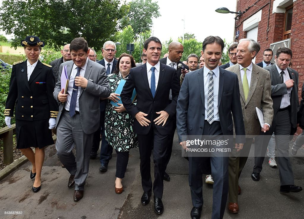 French Prime Minister Manuel Valls (C), flanked by French Housing Minister Emmanuelle Cosse (3rd L) and French Sports and Urban Affairs Minister Patrick Kanner (2nd L), visits the 'Cite 9' in Lens, on June 29, 2016, during a visit dedicated to the rehabilitation of Lens-Lievin mining area and the surroundings, including the renovation of housing. French urban planner Jean-Louis Subileau is in charge of the project and is expected to report next fall. / AFP / FRANCOIS