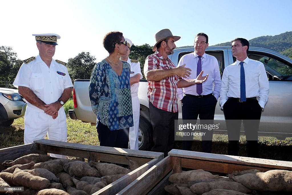 French Prime Minister Manuel Valls (R), French Minister for Overseas Territories George Pau-Langevin (2nd L) and French member of Parliament of New Caledonia Philippe Gomes (2nd R) visit the Delathiere farm on April 30, 2016 in La Foa, as part of Valls' visit to the French Pacific territory of New Caledonia. / AFP / Th��o Rouby