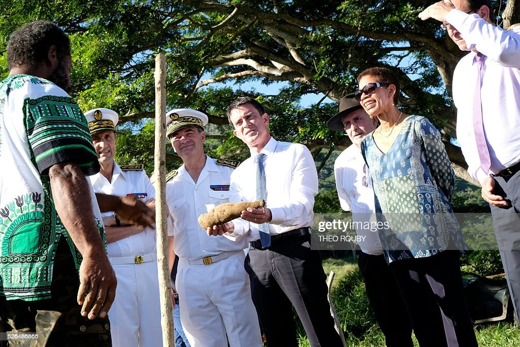 French Prime minister Manuel Valls (C) holds a piece of yam next to Overseas minister George Pau-Langevin (R) during their visit of a farm in La Foa, on April 30, 2016, as part of Valls' trip to the French Pacific territory. The visit comes amid political tension about New Caledonia's future and economic uncertainty following the sharp drop in the price of nickel. With the territory bound to have an independence referendum by 2018, Manuel Valls called on the territory's leaders not to waste time in useless skirmishes. / AFP / POOL / Th��o Rouby