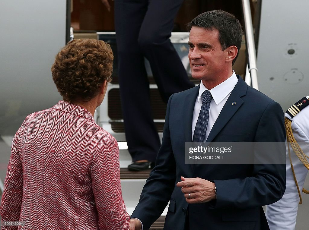 French Prime Minister Manuel Valls is greeted by French Ambassador to New Zealand Florence Jeanblanc-Risler (L) as he arrives in Auckland on May 1, 2016. Valls arrived in New Zealand on May 1 after visiting the French Pacific territory of New Caledonia, with officials in his delegation confirming that he will detour to Australia on May 2. / AFP / Fiona Goodall