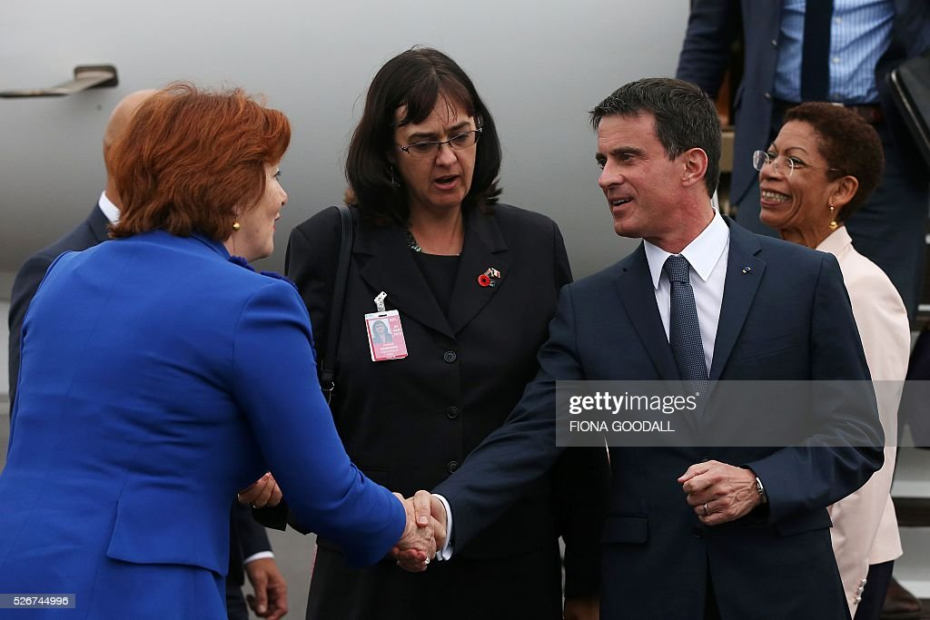 French Prime Minister Manuel Valls (R) is welcomed by New Zealand Minister for Arts, Culture and Heritage Maggie Barry (L) as he arrives in Auckland on May 1, 2016. Valls arrived in New Zealand on May 1 after visiting the French Pacific territory of New Caledonia, with officials in his delegation confirming that he will detour to Australia on May 2. / AFP / Fiona Goodall